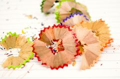 Beautiful piece of wood junk from sharpener crayon. Beautiful piece of wood junk from sharpener crayon on a paper and many colorful pieces Royalty Free Stock Photography