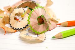 Beautiful piece of wood junk from sharpener crayon. Beautiful piece of wood junk from sharpener crayon on a paper and many colorful pieces Stock Photos