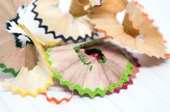 Beautiful piece of wood junk from sharpener crayon. Beautiful piece of wood junk from sharpener crayon on a paper and many colorful pieces Stock Image