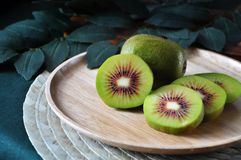 Beautiful Pieces of Red Kiwifruit on Wooden Plate. Close up pieces of red kiwifruit on wooden plate stock photos