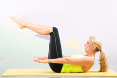 Beautiful pilates instructor with yellow yoga mat Stock Image
