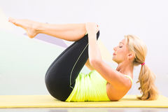 Beautiful pilates instructor with yellow yoga mat Royalty Free Stock Photo