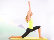 Beautiful pilates instructor with yellow yoga mat Royalty Free Stock Images