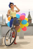 Beautiful pin up with balloons on a bicycle Stock Photography