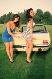 Beautiful pin up brunettes. Beautiful brunettes in a dresses  posing beside the car, cabriolet, Pin Up style, fashion photography, imitation film camera Royalty Free Stock Photography