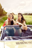Beautiful pin up brunettes. Beautiful brunettes in a swimsuits and leggings sits in the car, cabriolet, Pin Up style, fashion photography Royalty Free Stock Photography