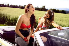 Beautiful pin up brunettes. Beautiful brunettes in a swimsuits and leggings sits in the car, cabriolet, Pin Up style, fashion photography Royalty Free Stock Photo