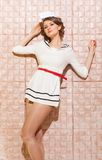 Beautiful pin-up girl dressed a sailor posing on pink background wall Royalty Free Stock Photography