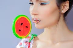 Beautiful pin-up girl holding sweet lollipop Stock Image