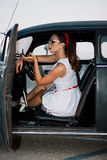 Beautiful pin-up girl inside vintage car.  stock photography