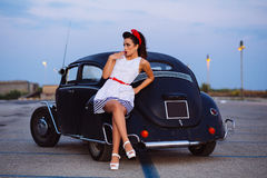 Beautiful pin-up girl posing with hot road car Royalty Free Stock Photography