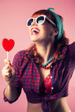 Beautiful pin-up girl posing with red heart-shaped lollipop agai Royalty Free Stock Photo