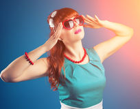 Beautiful pin-up girl posing with red heart-shaped sunglasses ag Royalty Free Stock Image