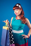 Beautiful pin-up girl posing with shopping bags against blue bac Royalty Free Stock Images