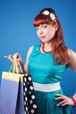 Beautiful pin-up girl posing with shopping bags against blue bac Royalty Free Stock Image