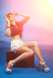 Beautiful pin-up girl posing with vintage suitcase against blue royalty free stock image