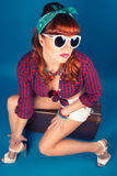 Beautiful pin-up girl posing with vintage suitcase against blue Royalty Free Stock Photography