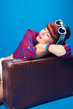 Beautiful pin-up girl posing with vintage suitcase against blue Stock Photography