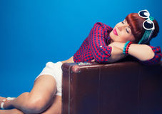 Beautiful pin-up girl posing with vintage suitcase against blue Royalty Free Stock Photos