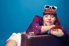 Beautiful pin-up girl posing with vintage suitcase against blue Stock Photos