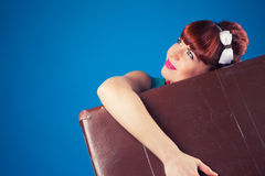 Beautiful pin-up girl posing with vintage suitcase against blue Royalty Free Stock Images