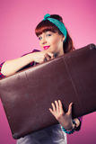 Beautiful pin-up girl posing with vintage suitcase against pink Stock Image
