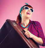 Beautiful pin-up girl posing with vintage suitcase against pink Royalty Free Stock Photo