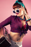 Beautiful pin-up girl posing with vintage suitcase against pink Stock Photos