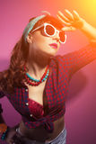 Beautiful pin-up girl posing with white sunglasses against pink Royalty Free Stock Photo
