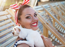Beautiful pin up girl with puppy near the swimming pool Royalty Free Stock Photo