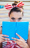 Beautiful pin up girl reading the book near the swimming pool Royalty Free Stock Photo
