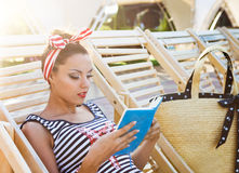 Beautiful pin up girl reading the book near the swimming pool Stock Photo