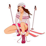 Beautiful pin-up girl with skis. Tying shoelaces isolated on a white background Royalty Free Stock Photography