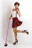 Beautiful pin up girl. Beautiful young woman dressed in pin up style with retro makeup and hairstyle standing with pink mop. Full body studio shot over beige stock photo