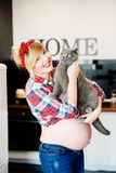 Beautiful pin up stylized young pregnant woman in kitchen Stock Image