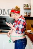 Beautiful pin up stylized young pregnant woman in kitchen. Measuring her belly with measure tape Stock Photo