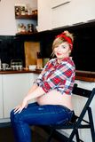 Beautiful pin up stylized young pregnant woman s. Itting on the chair in kitchen Stock Photography