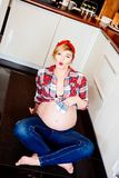 Beautiful pin up stylized young pregnant woman. Sitting on the floor in kitchen and holding little baby shoes Stock Photos