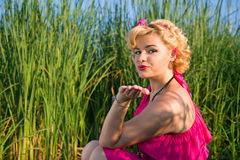 Beautiful pin-up woman blowing a kiss Stock Photo