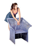Beautiful pin up woman posing on old cane chair Royalty Free Stock Photography