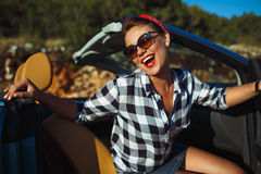 Beautiful pin up woman sitting in cabriolet, enjoying trip on lu Stock Photo