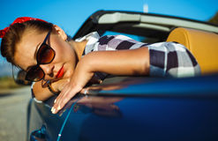 Beautiful pin up woman sitting in cabriolet, enjoying trip on lu Royalty Free Stock Images