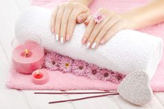 Beautiful pinc manicure with chrysanthemum flower and towel on the white wooden table. spa Royalty Free Stock Image