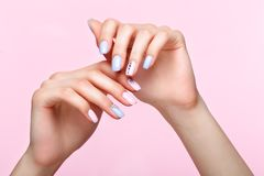 Beautiful pink and blue manicure with crystals on female hand. Close-up. Picture taken in the studio royalty free stock photo