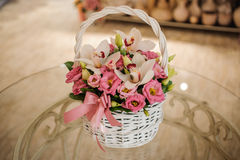 Beautiful pink bouquet of mixed flowers in basket on table. Beautiful pink bouquet of mixed flowers in basket on glass table Royalty Free Stock Images