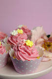 Beautiful pink decorated cupcakes on pink cake stand -  Vertical close up with bokeh. Royalty Free Stock Photos