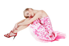 Beautiful pink dress. Beautiful blond girl in stylish pink dress sitting on white background and smiling Royalty Free Stock Images