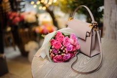 Beautiful pink flowers near the stylish handbag on the table. Beautiful pink flower composition near the stylish handbag on the table against the bright Royalty Free Stock Photography
