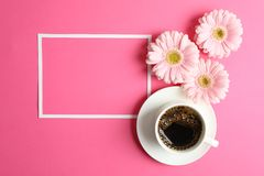 Beautiful pink gerbera flowers, cup of coffee and frame on color background, top view royalty free stock photography