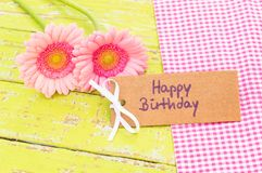 Pastel pink flowers and greeting card Happy Birthday. Beautiful pink gerbera flowers with Happy Birthday greeting card on wooden table background royalty free stock photo
